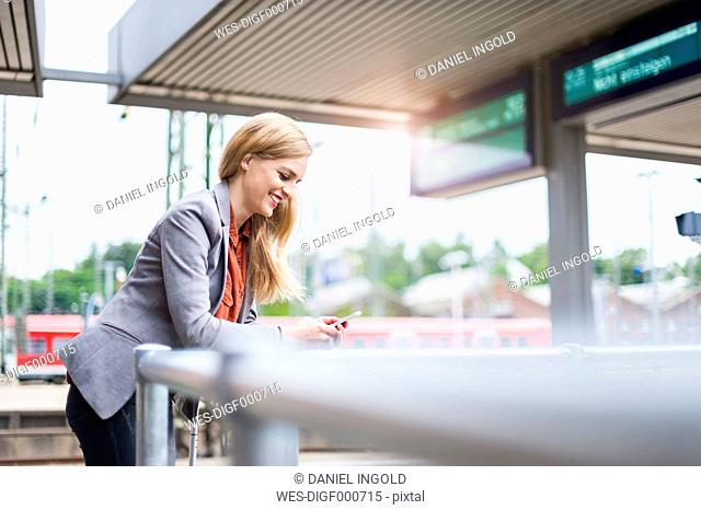 Smiling young woman at platform looking on cell phone