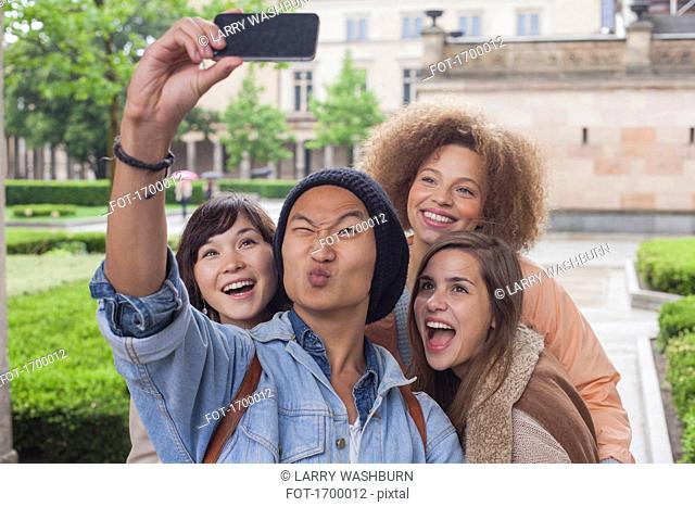 Young man making face while taking selfie with female friends, Berlin, Germany