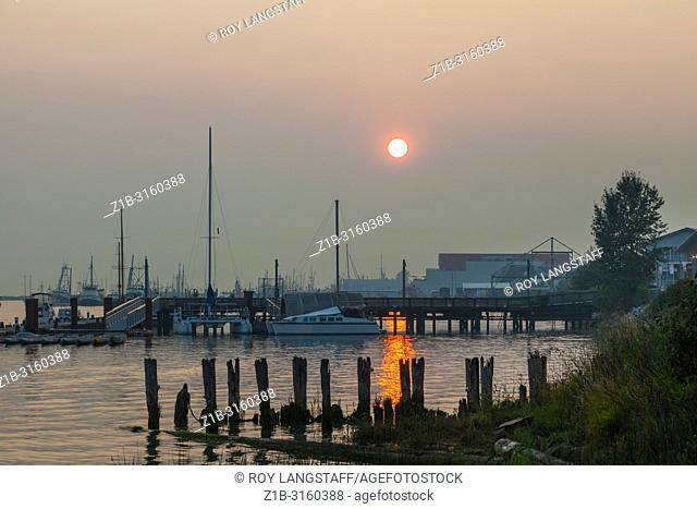 Evening sun struggling to penetrate the forest fire smoke over Steveston, British Columbia