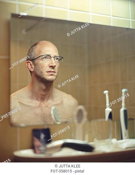 Man staring at reflection in bathroom mirror