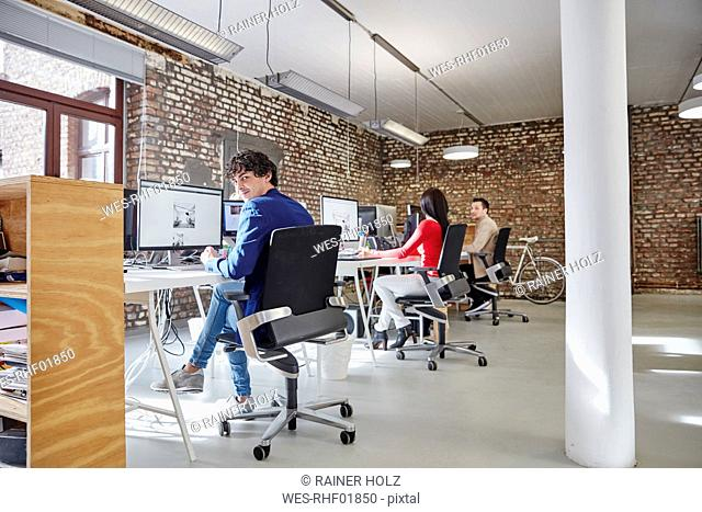 Group of people working in creative office, looking content