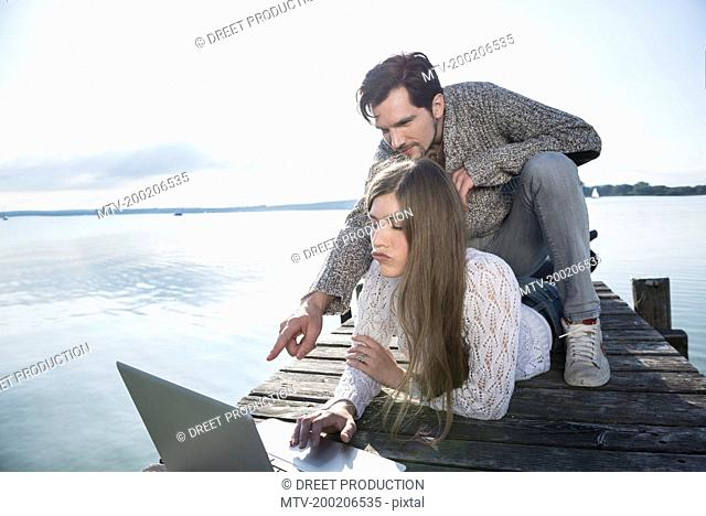 couple together lake outdoors working computer