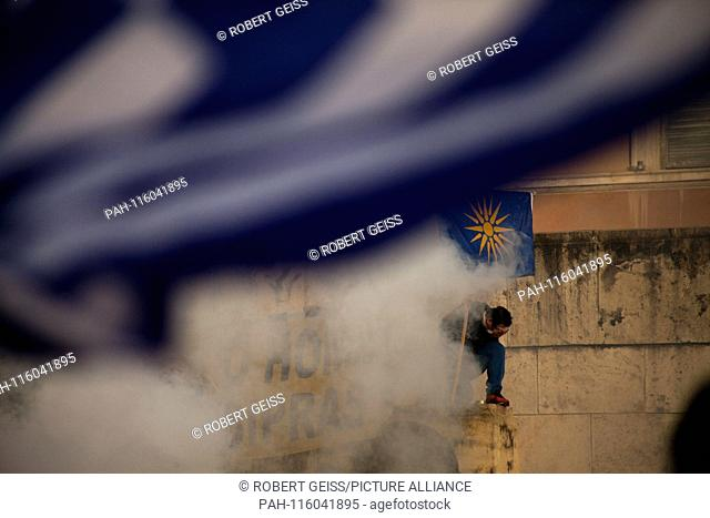 Greek man with flag Star of Vergina, in front of parliament, after tear gas during protest against recognition of the name FYROM as North Macedonia