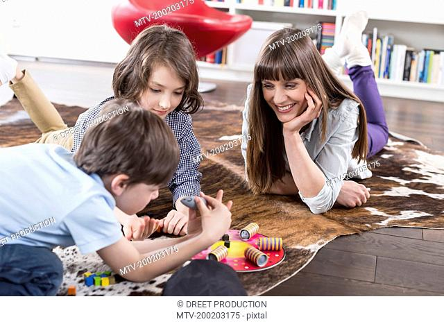 Mother playing board game with her children