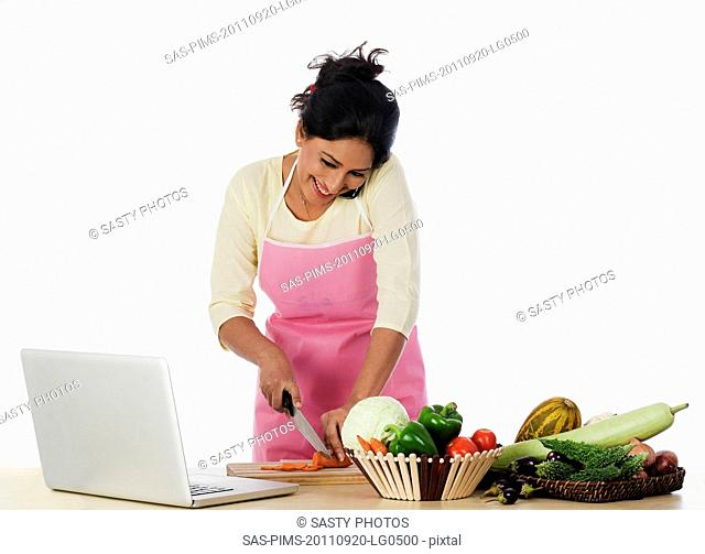 Woman cutting vegetables, using a laptop and a mobile phone