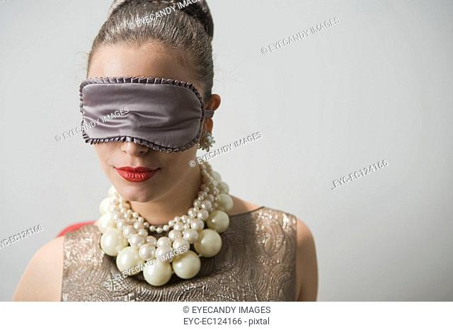 Close-up of a young woman wearing blindfold, puckering