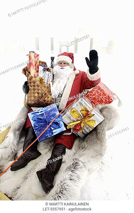 Santa Claus sits in a sledge full of Christmas presents  Behind the SnowCastle of Kemi