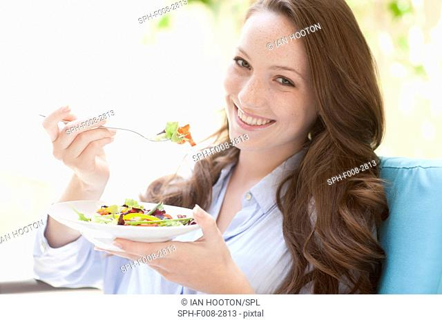 MODEL RELEASED. Young woman eating a salad