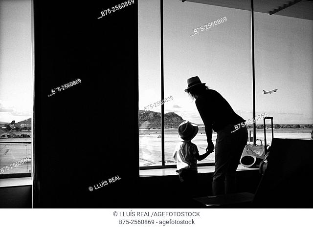 Back view of a young woman with holding the hand of a child, looking through a window on the airport the takeoff of an airplane