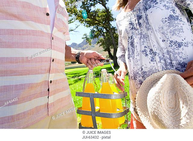 Senior couple with picnic bottles in countryside