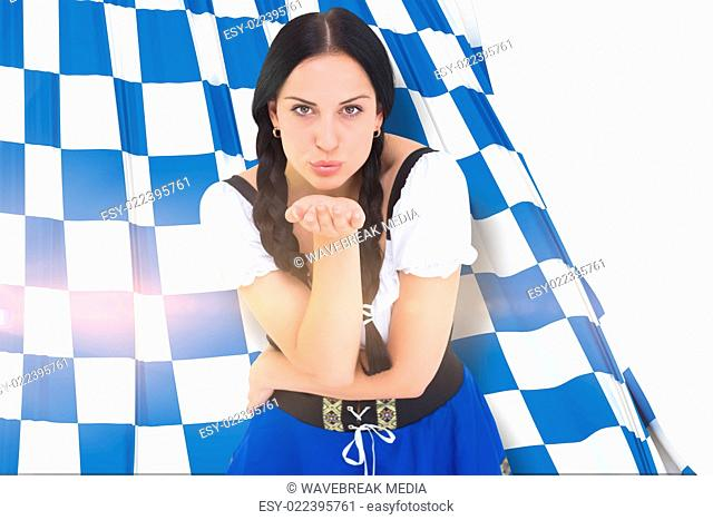 Composite image of pretty oktoberfest girl blowing a kiss