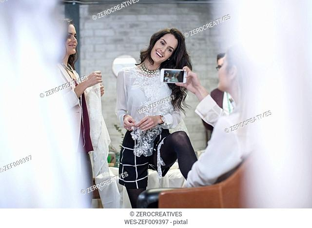 Woman taking smartphone picture in fashion showroom