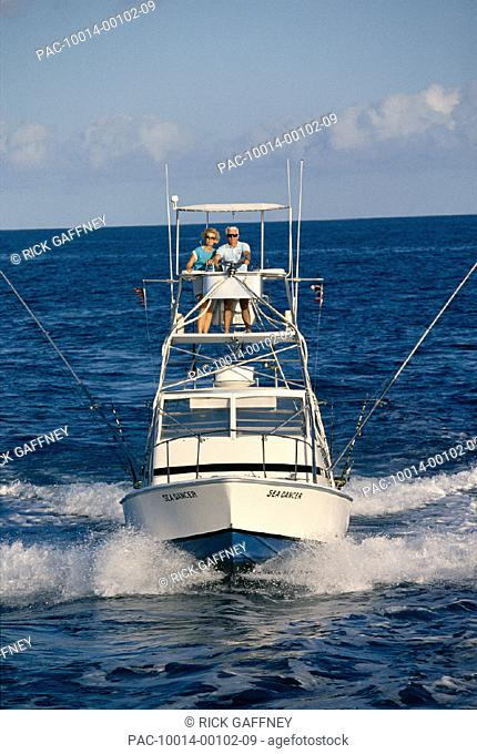 Hawaii, front view of sport fishing boat, senior couple in flying bridge A14E