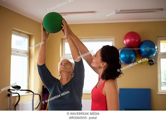 Female therapist assisting senior woman with ball