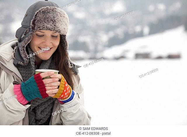 Smiling woman drinking coffee in snow