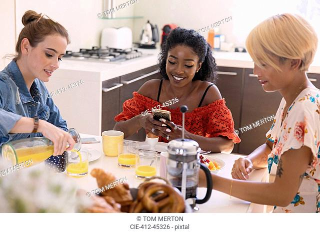 Young women friends enjoying breakfast at kitchen table