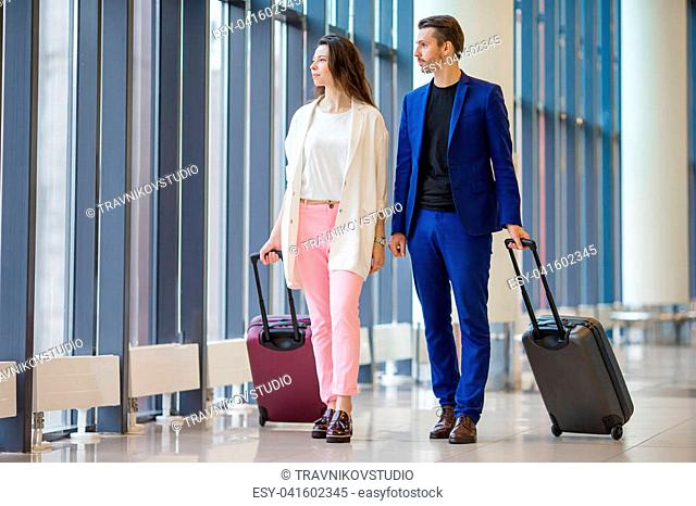 Young couple in international airport walking with her luggage
