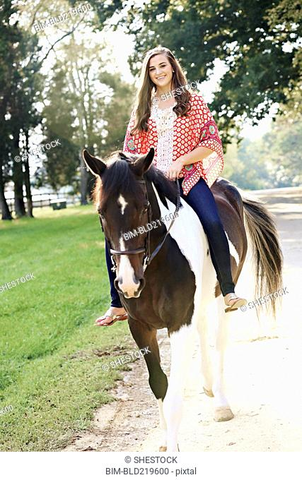 Smiling woman riding horse on path