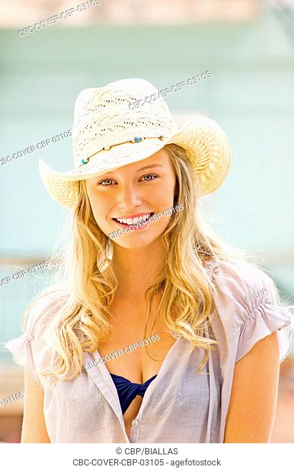 Portrait of Young Woman with Straw Hat Looking at Camera