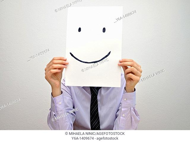 Businesswoman holding card with smiley face in front of face