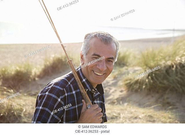 Portrait smiling senior man with fishing rod walking on sunny beach