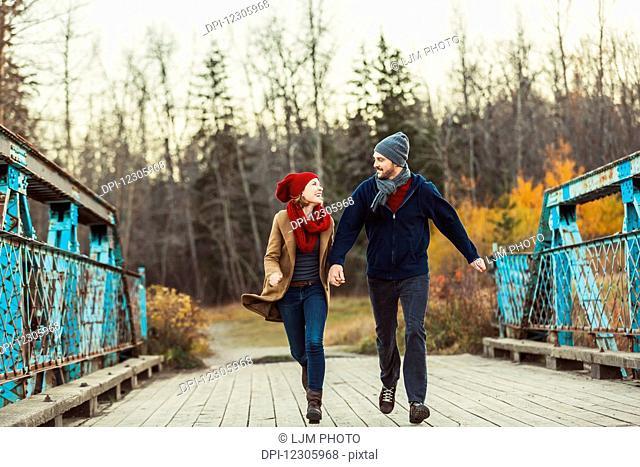 A young couple running on a bridge during the autumn season in a city park; Edmonton, Alberta, Canada