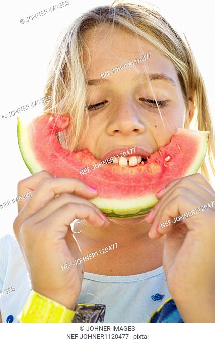 Girl eating slice of watermelon, close-up