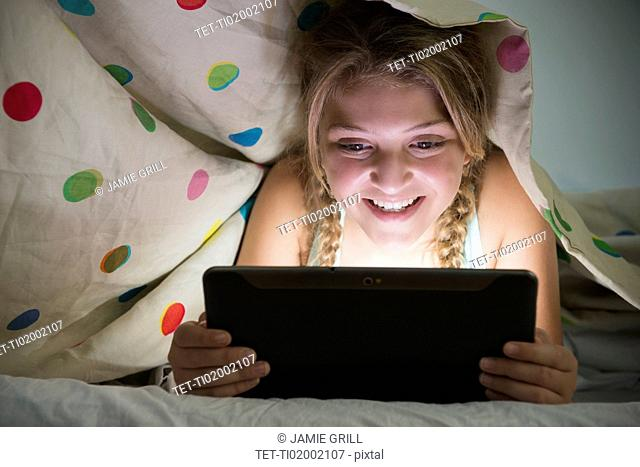 Girl (12-13) using tablet in bed