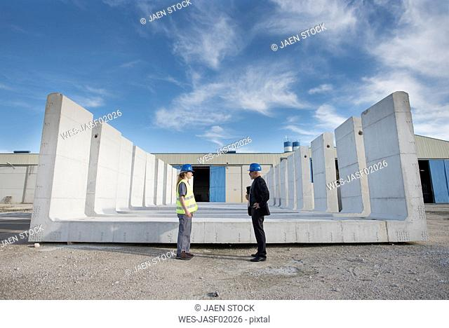 Businessman and female worker standing on industrial site in front of concrete blocks