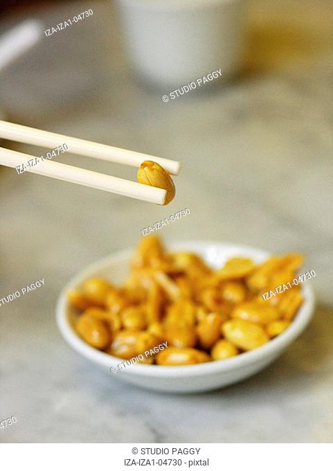 Close-up of a person's hand picking a peanut from a bowl with chopsticks
