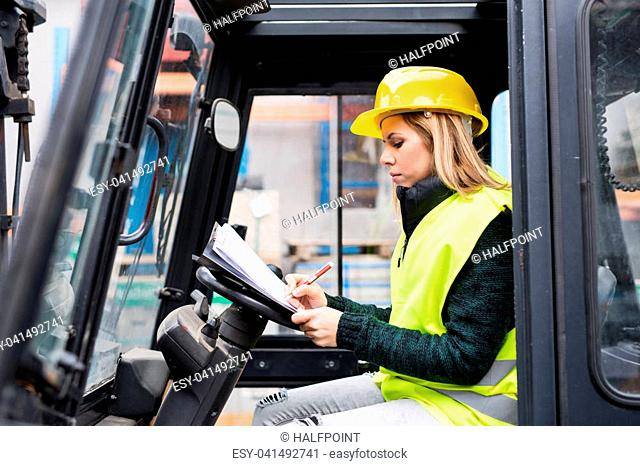 Female forklift truck driver in an industrial area. A woman sitting in the fork lift outside a warehouse, making notes