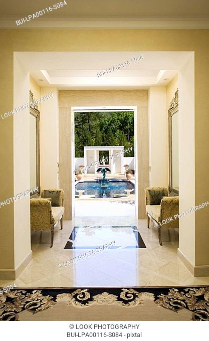 Interior of a marble hallway leading to a pool