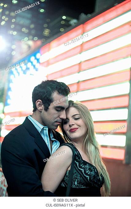 Neon american flag and romantic young couple, New York City, USA