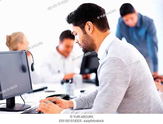 Business man working on computer with colleagues in background