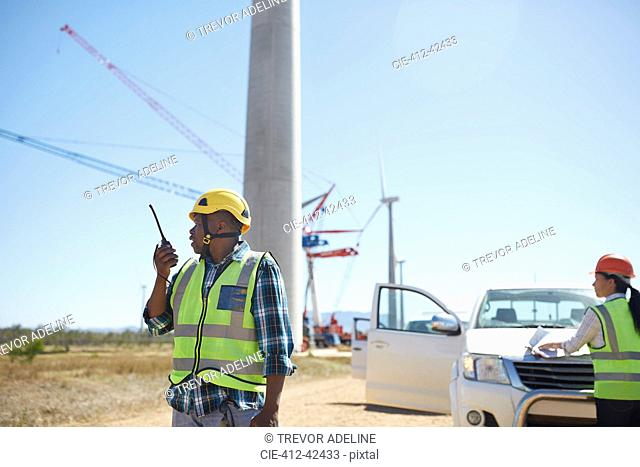 Male engineer with walkie-talkie at sunny wind turbine power plant