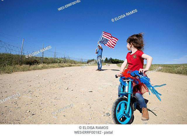 Girl with bicycle and man with American flag on path in remote landscape