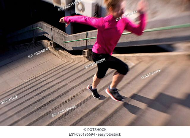 sporty woman running onsteps at early morning jogging