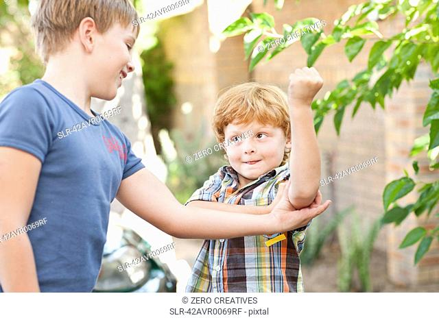 Boy feeling brothers biceps outdoors