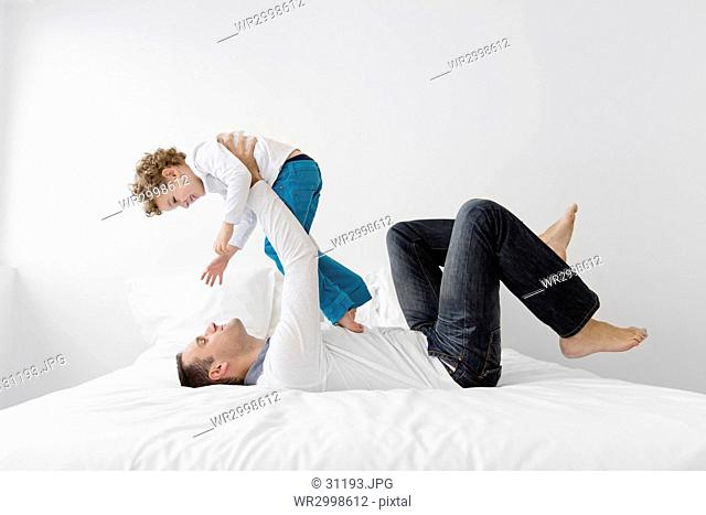 Smiling man lying on his back on a bed, holding aloft young boy