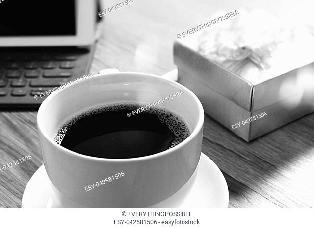 Coffee cup and Digital table dock smart keyboard,gold gift box and round wood tray,color pencil on wooden table,filter effect,black white