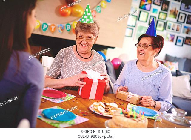 Daughter talking to mother and friend at birthday party