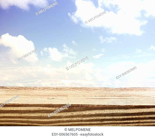 Beautiful blue cloudscape sky background with a wooden deck board foreground