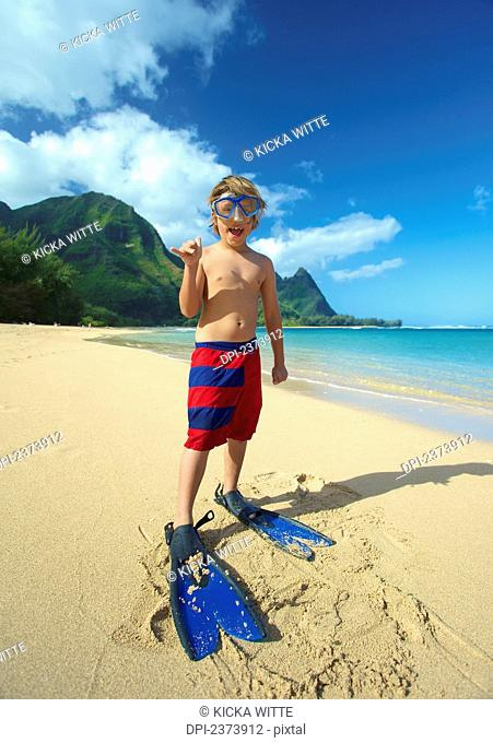 A boy on the beach with snorkelling gear; Kauai, Hawaii, United States of America