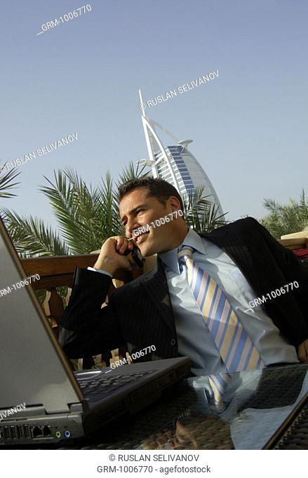 Businessman using mobile phone in Dubai (Burj Al Arab hotel in background)