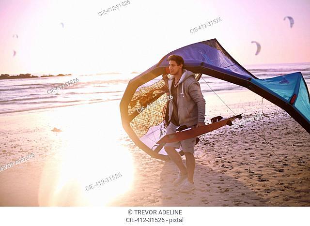 Man carrying kiteboarding equipment on sunset beach