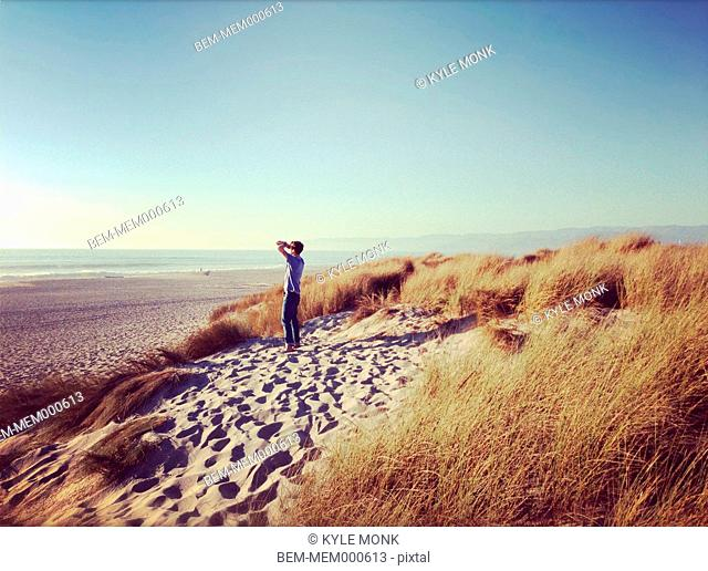 Man overlooking ocean and beach, Oxnard, California, United States