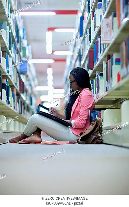 Female student sitting on floor in library writing notes