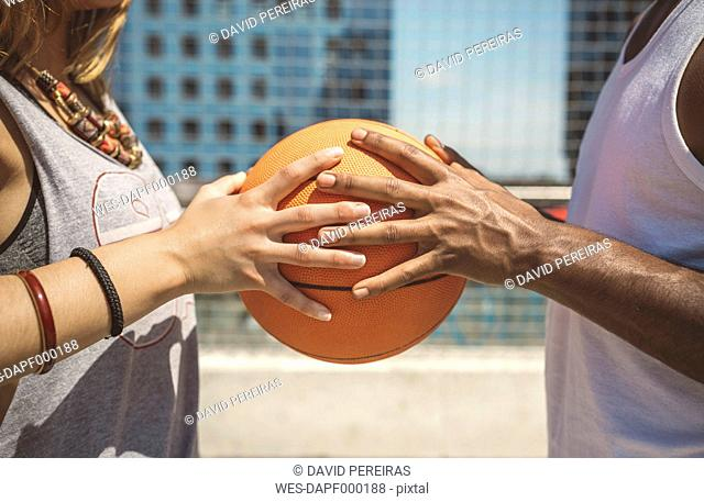 Young couple holding basketball