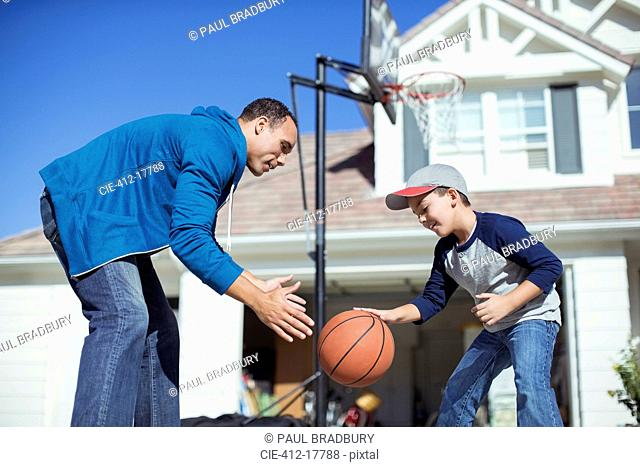 Father and son playing basketball in sunny driveway