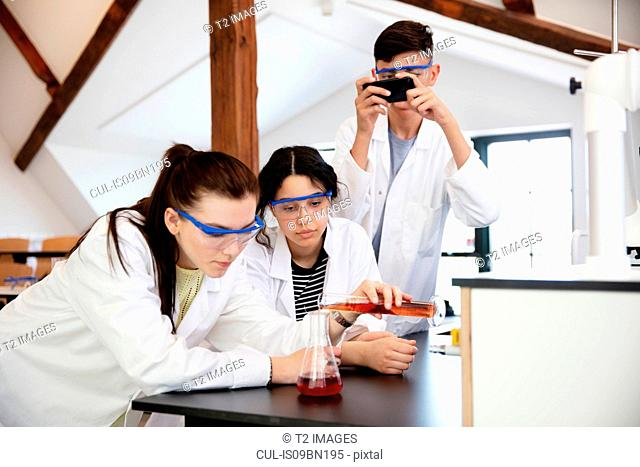 Students pouring sample into flask in laboratory